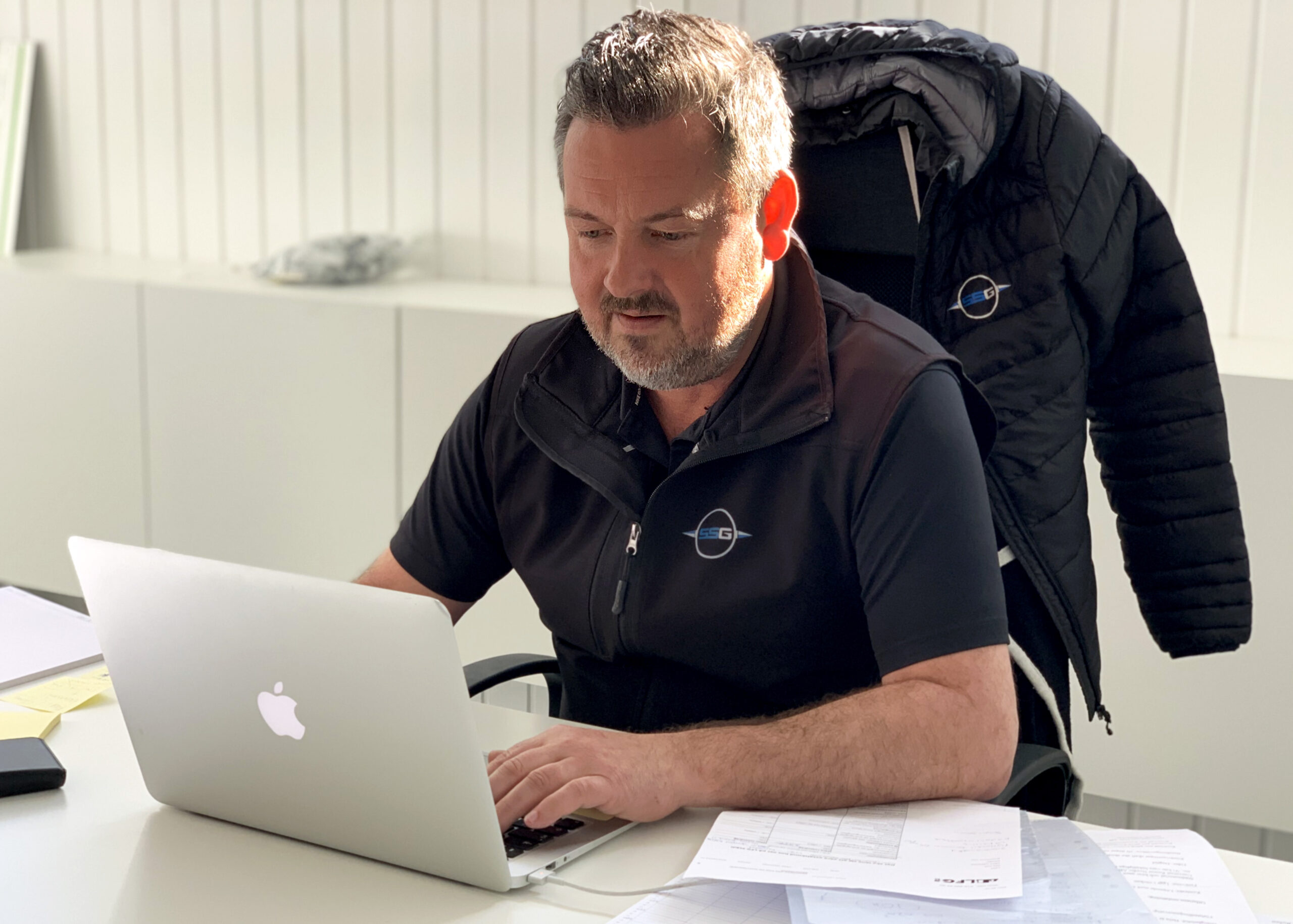 En man klädd i svart pikétröja sitter framför ett vitt skrivbord och skriver på en dator