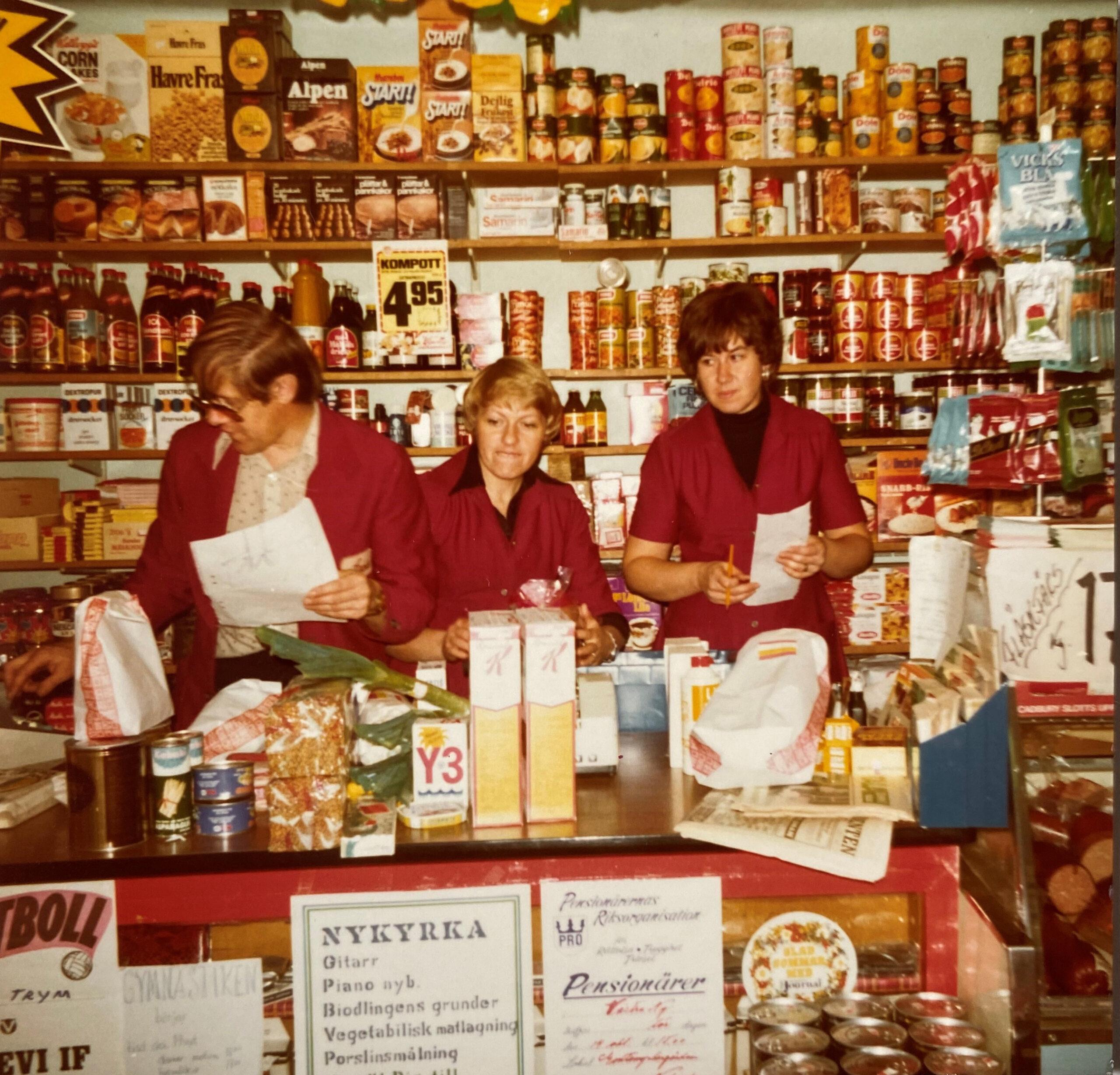 Ett foto från 70-talet på tre personer som står bakom en affärsdisk. Hyllorna på väggen är fulla av varor.