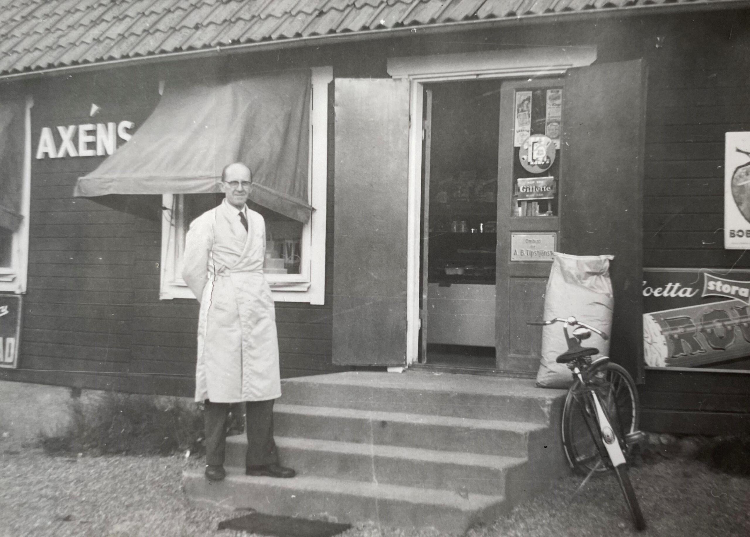 Ett svartvitt gammalt foto på en stolt man klädd vit rock poserandes utanför en byggnad som det står Axéns på.