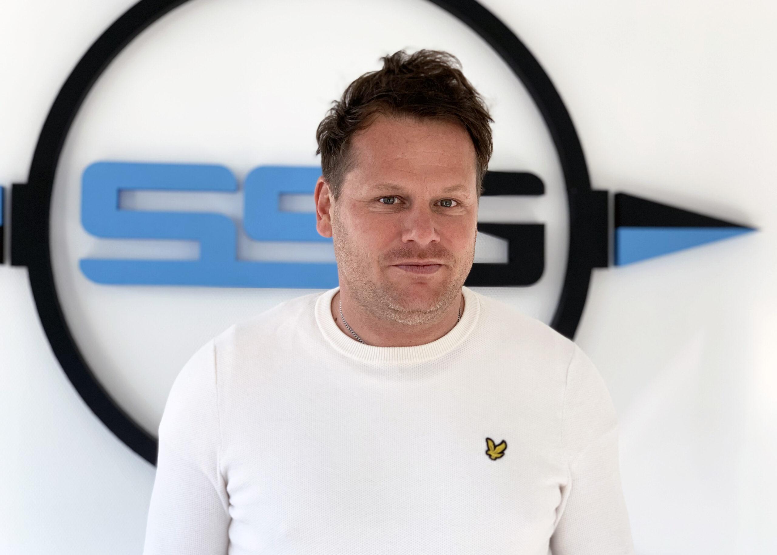 En man klädd i vit tröja ser lite finurlig ut framför en stor svartblå logotype på väggen.