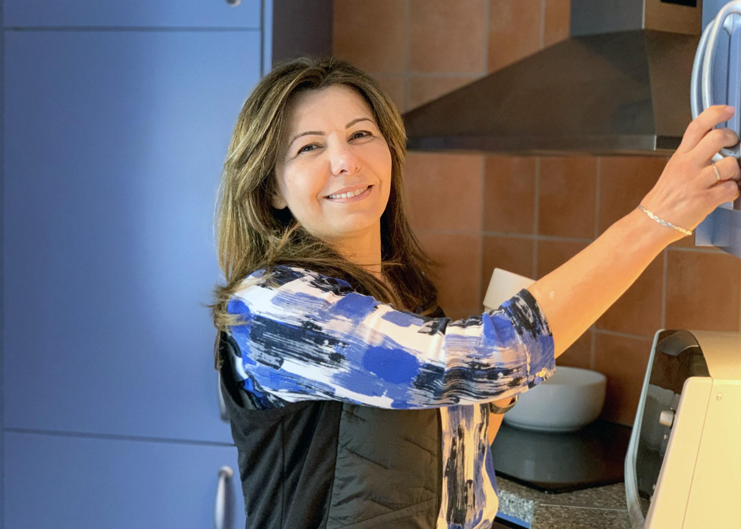 En leende kvinna klädd i blått och svart, håller i handtaget till ett skåp