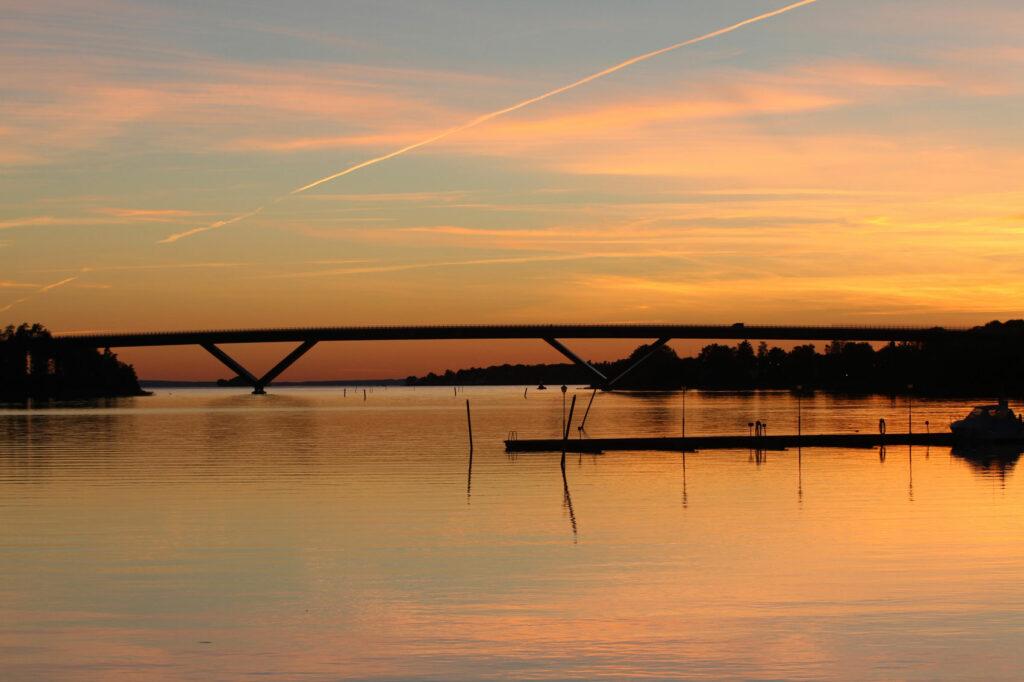 Solnedgång över stilla vatten. I bakgrunden går en stor bro över sundet.