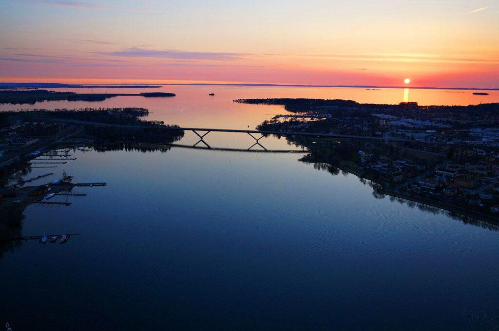 Drönarbild över en vik i härliga färger i solnedgång med fantastiska färger i blått, lila, rosa och orange. Längre bort ser man en stor bro som löper över ett sund.