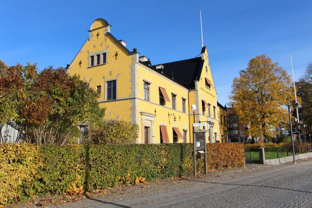Stor äldre gul byggnad en solig höstdag.