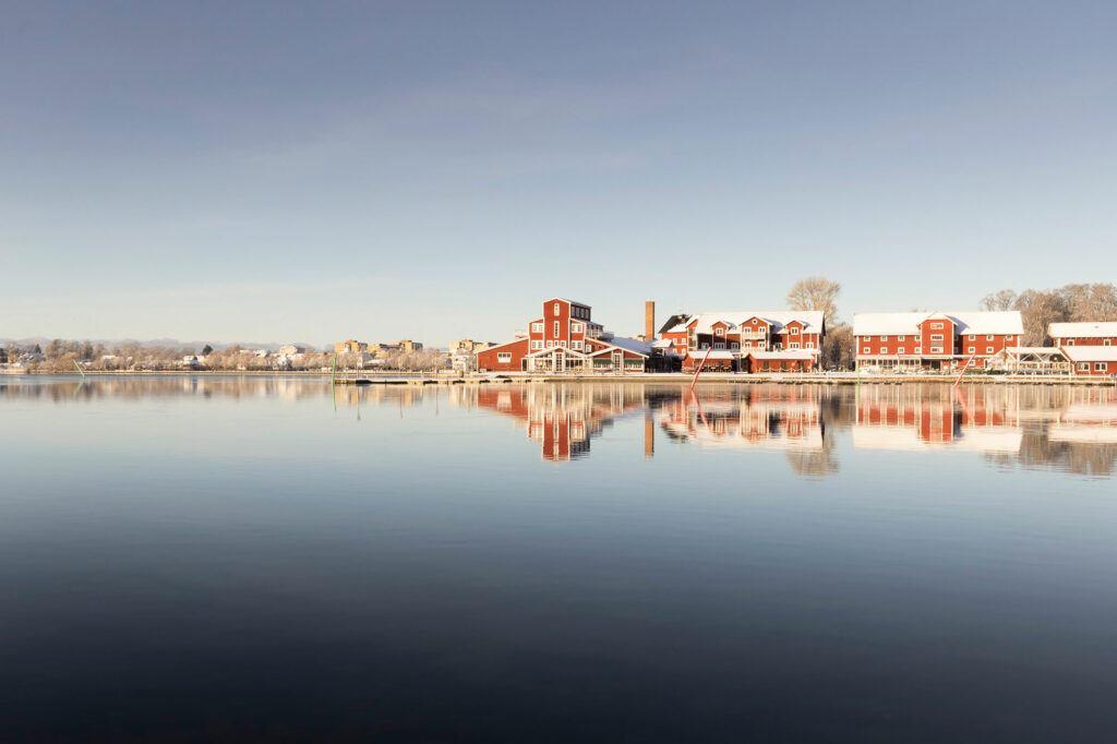Vatten som ligger spegelblankt en vintermorgon. På andra sidan vattnet ligger en pir med röda träbyggnader.