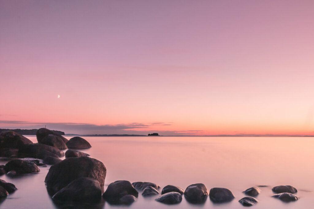 Solnedgång över stilla vatten. Himlen skiftar i lila, rosa och orange och speglar sig i vattnet.