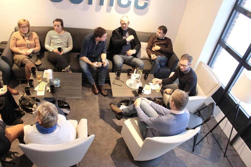 Människor sitter i soffor och fåtöljer i kontorsmiljö och samtalar.