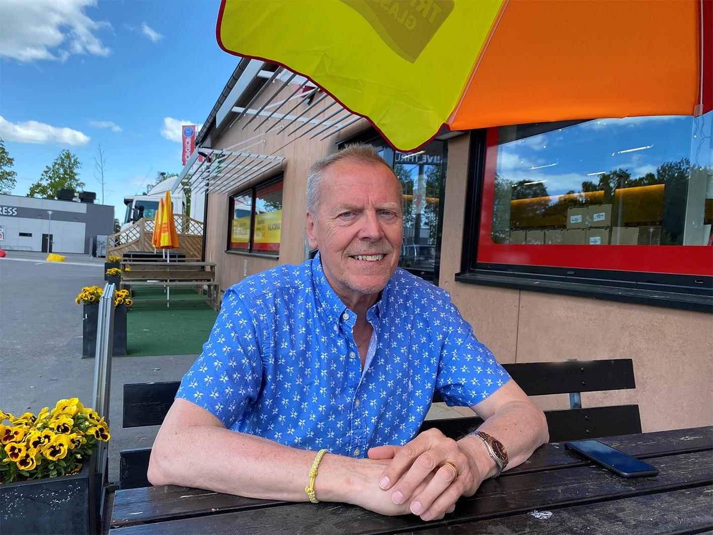 Ett foto på en leende man som sitter under ett färgglatt parasoll.