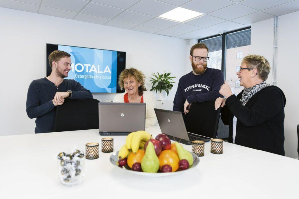 Två män och två kvinnor står vid ett stort bord. På bordet står två datorer, ett fruktfat och några ljuslyktor.