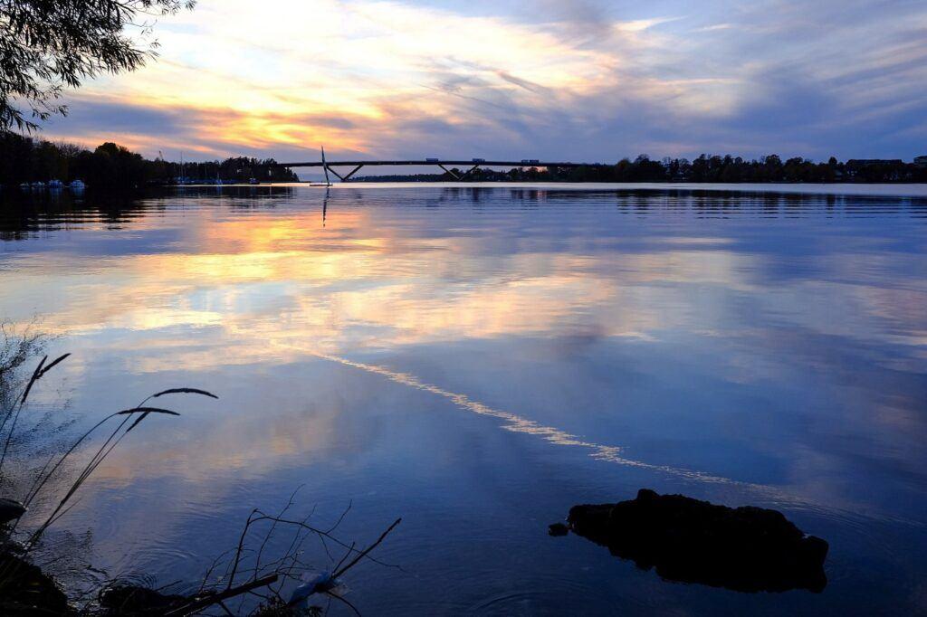 Vacker vy över vattnet där himlen speglar sig i det stilla vattnet.