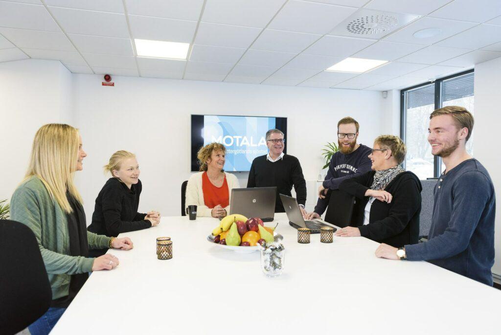 7 personer har möte kring ett bord.