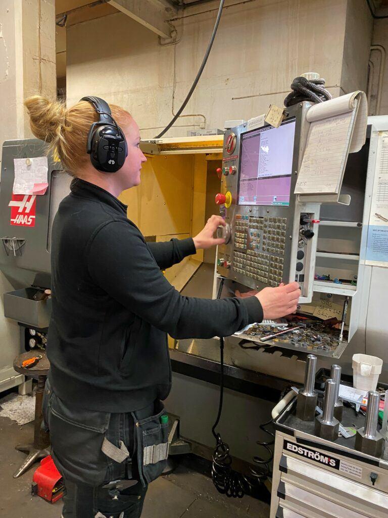 En fokuserad kvinna klädd i arbetskläder, rattar en dator som sitter fast på en stor maskin.