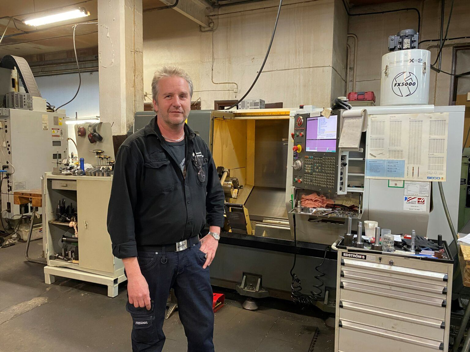 En svartklädd man ler in i kameran, ståendes framför en stor maskin